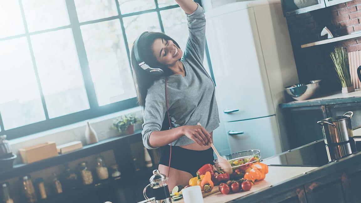 woman wearing headphones makes breakfast and dances