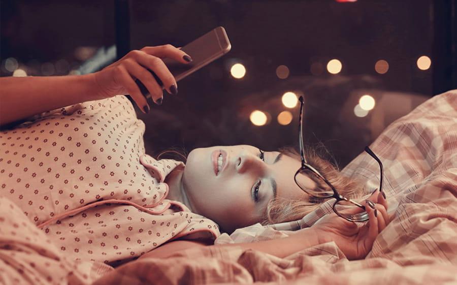 mujer utilizando el teléfono celular en la cama