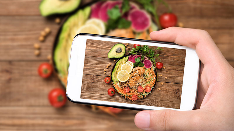 hand taking cell phone picture of healthy fats in salad