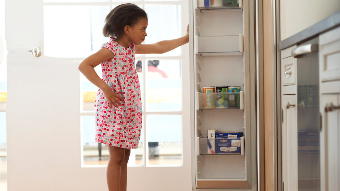 chica mirando en la despensa de la cocina