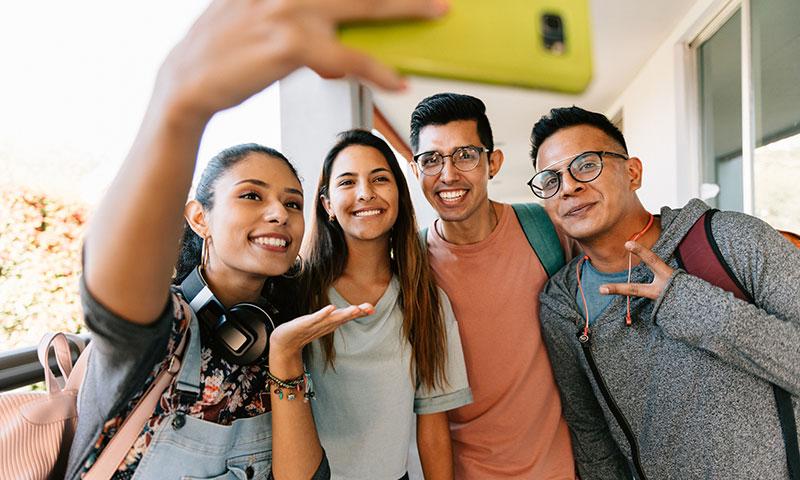 Estudiantes universitarios felices se toman una selfi al aire libre