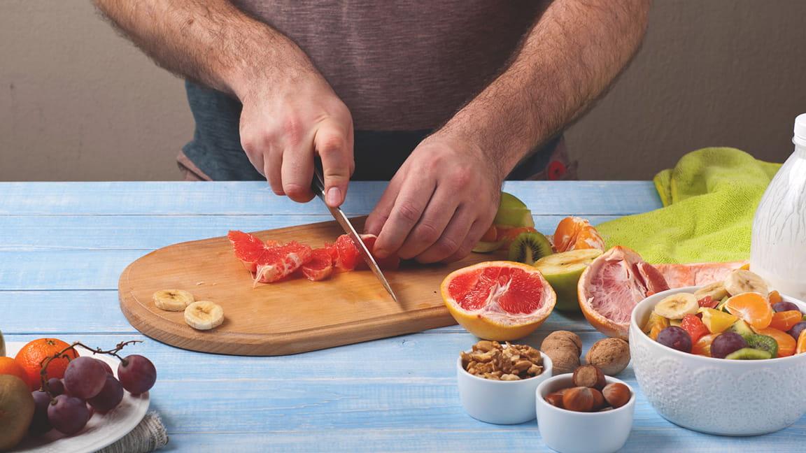 hombre picando frutas y verduras