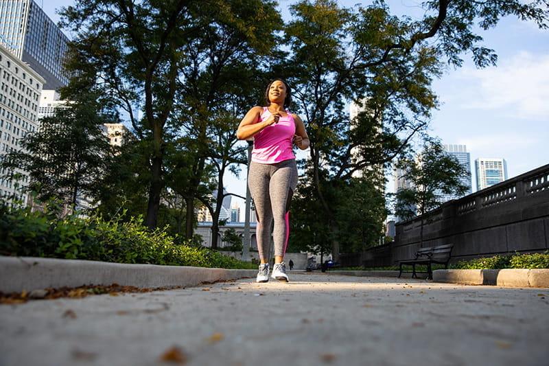mujer caminando en una acera en el centro de la ciudad