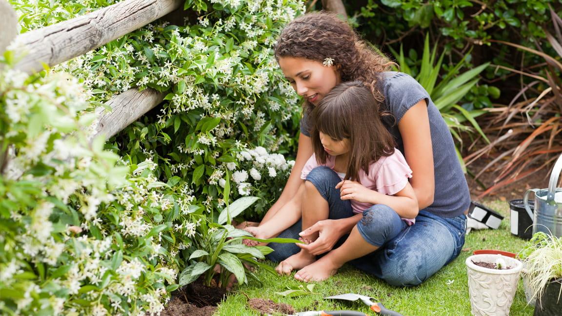 madre e hija plantando en el jardín