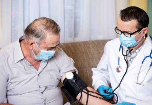 male patient having blood pressure checked by male doctor