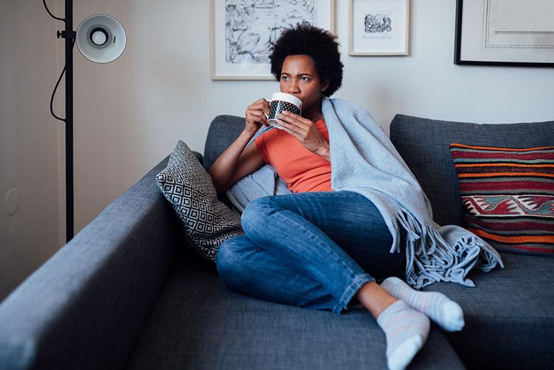 mujer enferma bebiendo en el sofá