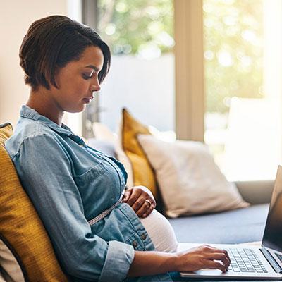 mujer embarazada usa una computadora portátil en el sofá
