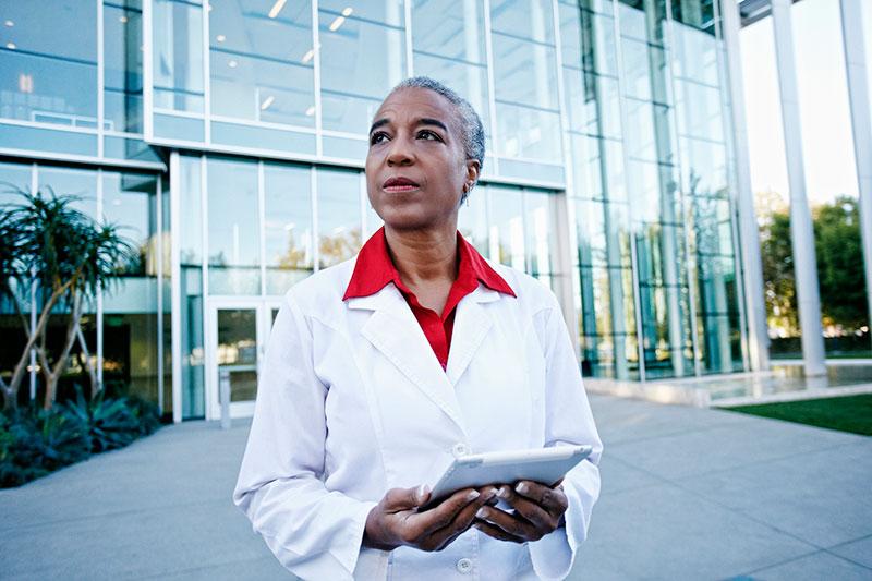 médica o investigadora sostiene una tableta fuera de un edificio GettyImages-738778729