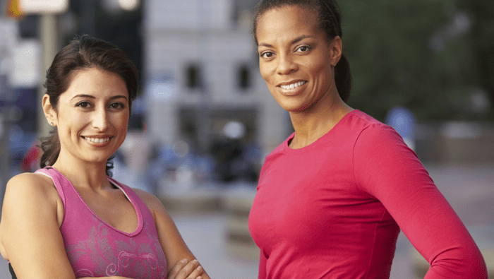 two women in workout clothes smiling at the viewer