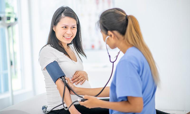 nurse checks pregnant woman's blood pressure