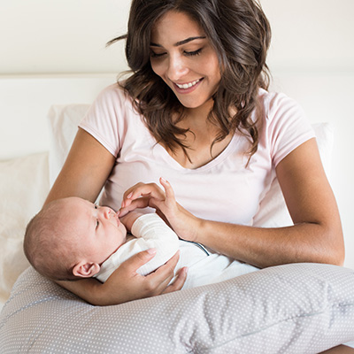 young mother holds baby in bed
