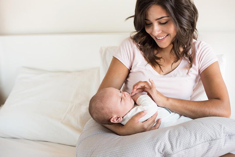 una madre joven sonriente que sostiene a su bebé en la cama