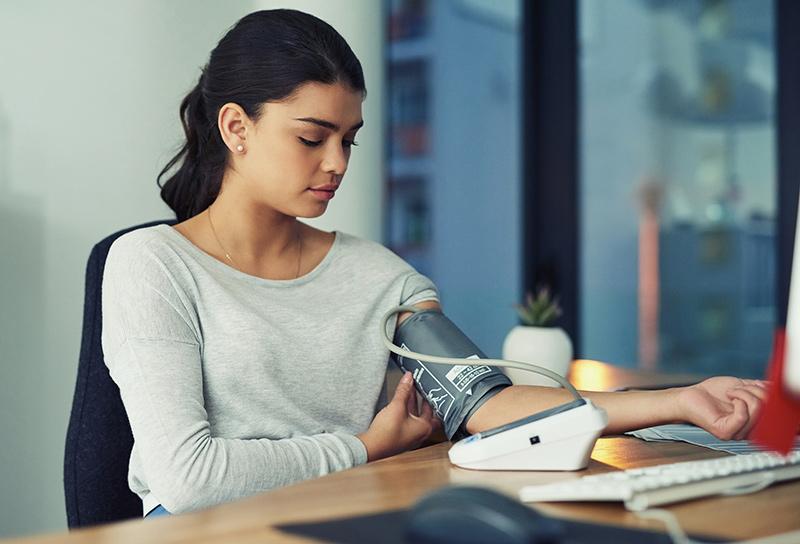 mujer comprobando su presión arterial en el trabajo