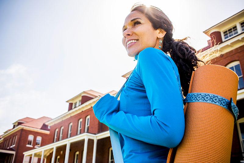 mujer con alfombrilla de yoga sobre el hombro en una calle urbana