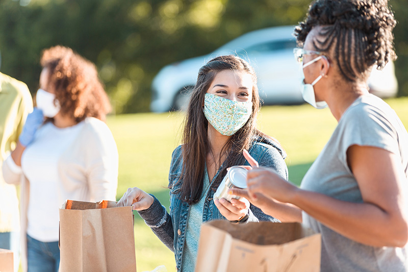voluntarios con mascarillas distribuyen alimentos enlatados