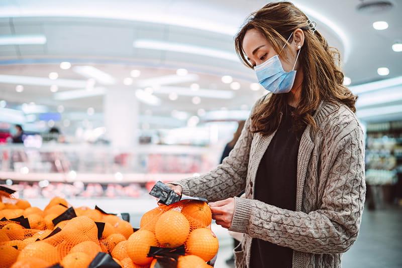 mujer comprando con una mascarilla