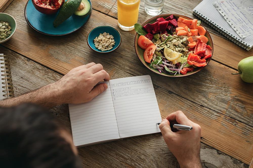 hombre planificando comidas en una mesa con comida