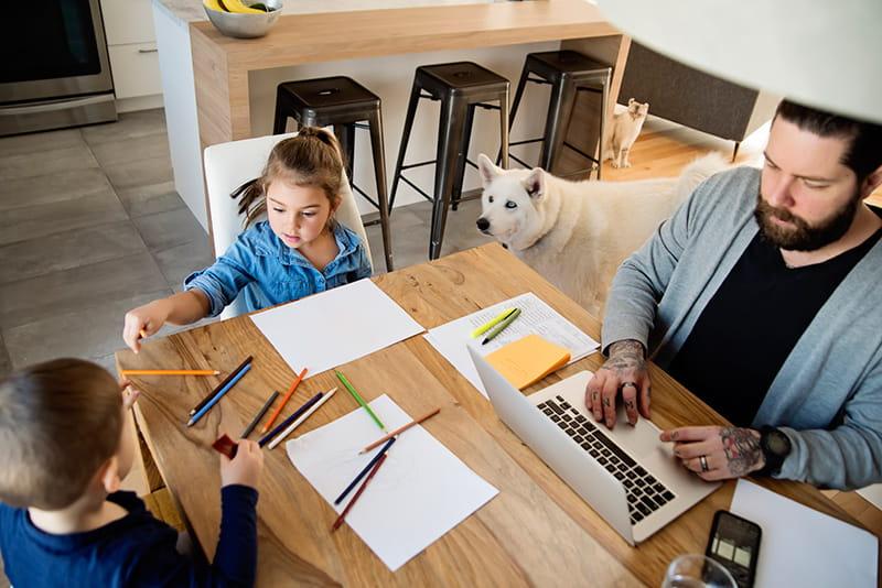 un padre utiliza su computadora portátil en la cocina mientras los niños dibujan al perro