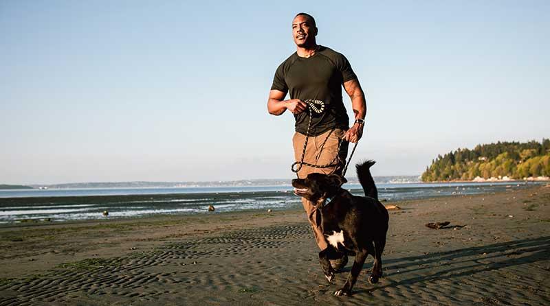 hombre corriendo con su perro en la playa