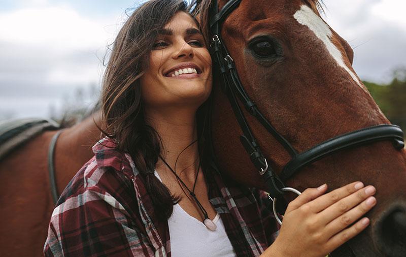 mujer sonriente abraza a caballo