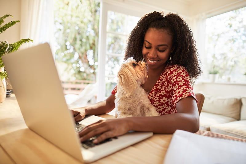 mujer usando su computadora portátil con su perro