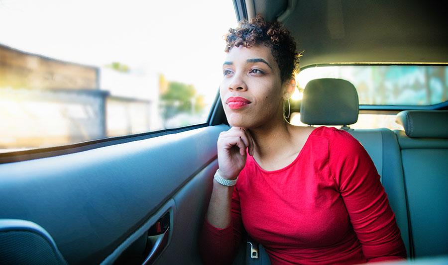una mujer tranquila mira por la ventana del automóvil
