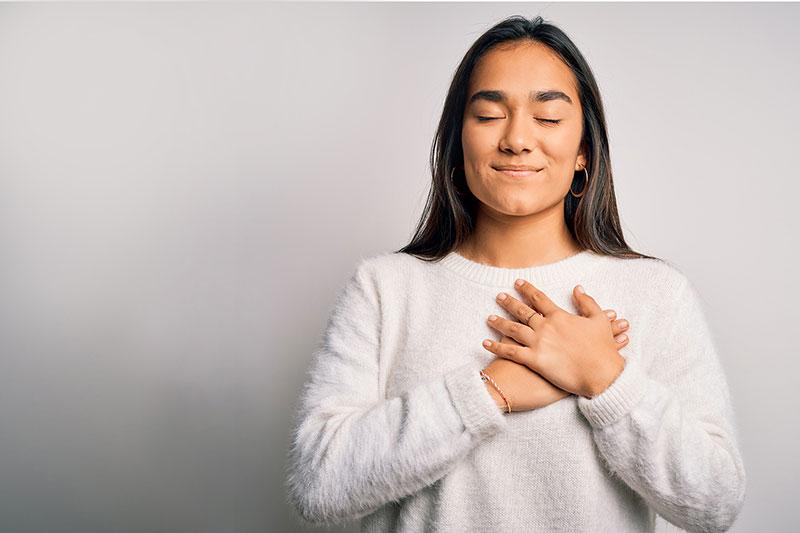 mujer agradecida con la mano sobre el corazón