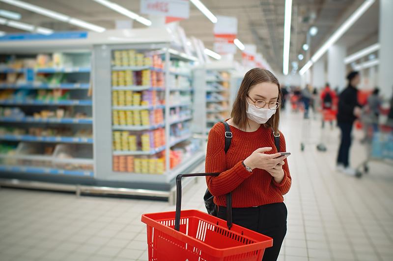 Una compradora lee la lista de productos certificados por Heart-Check mientras hace la compra