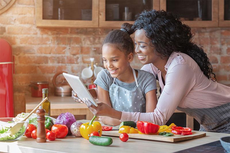 Una mamá y su hija leen una receta en una tableta mientras cocinan