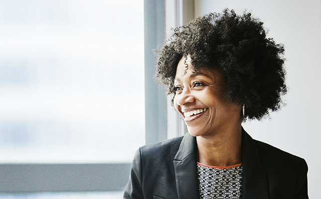 Smiling business woman in front of sunny window