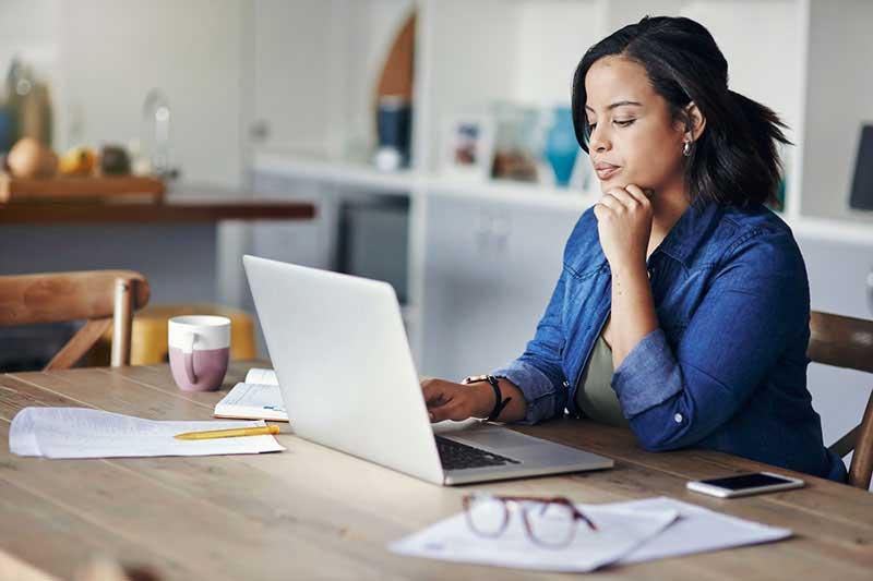 mujer sentada frente una mesa mirando una computadora portátil