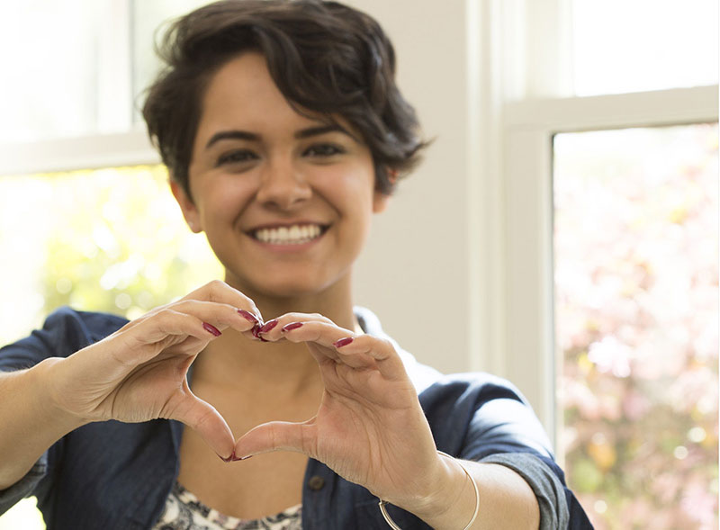 smiling Woman making heart hand gesture