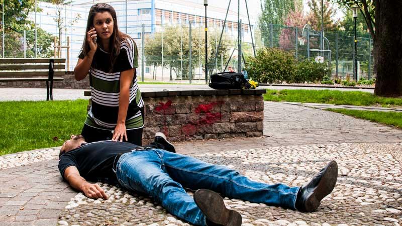 mujer llamando para pedir ayuda para un hombre que está en el suelo