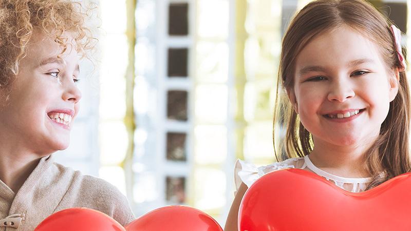 Dos niñas con corazones rojos grandes