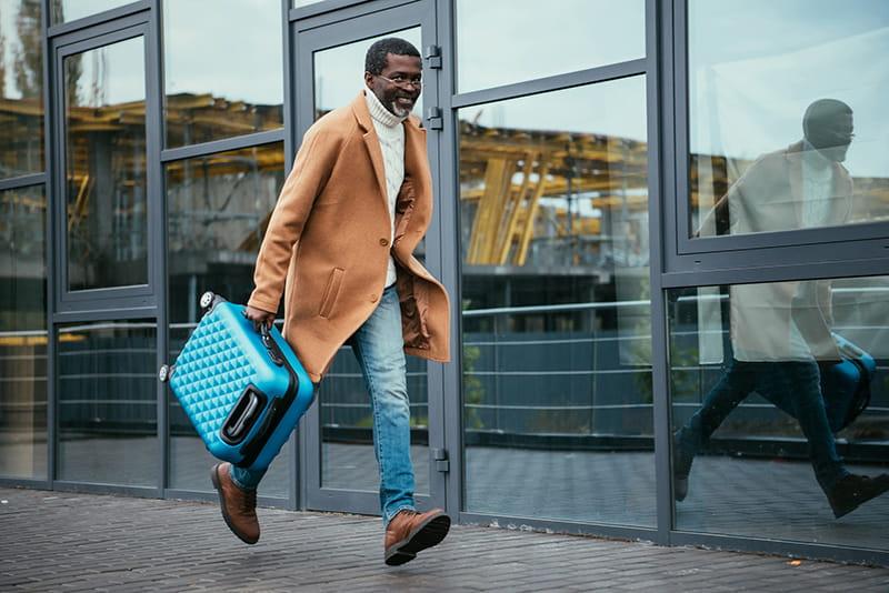 Pasajero en un aeropuerto corriendo con una maleta