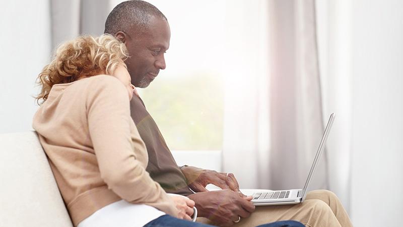 pareja mirando la pantalla de una computadora portátil