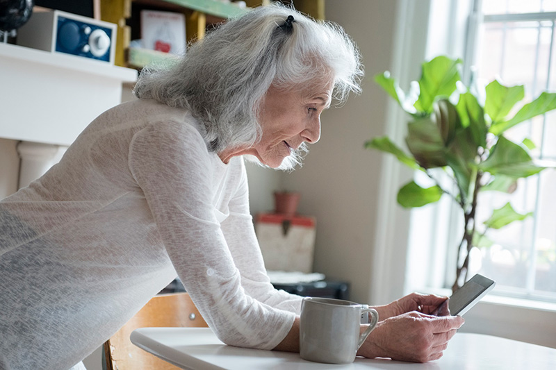 Woman looking at her cell phone while leaning on kitchen counter