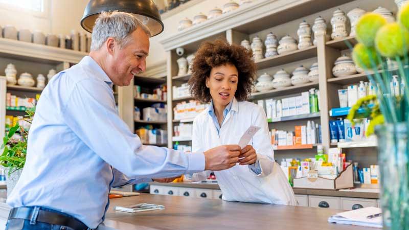 hombre hablando con farmacéutico sobre la receta