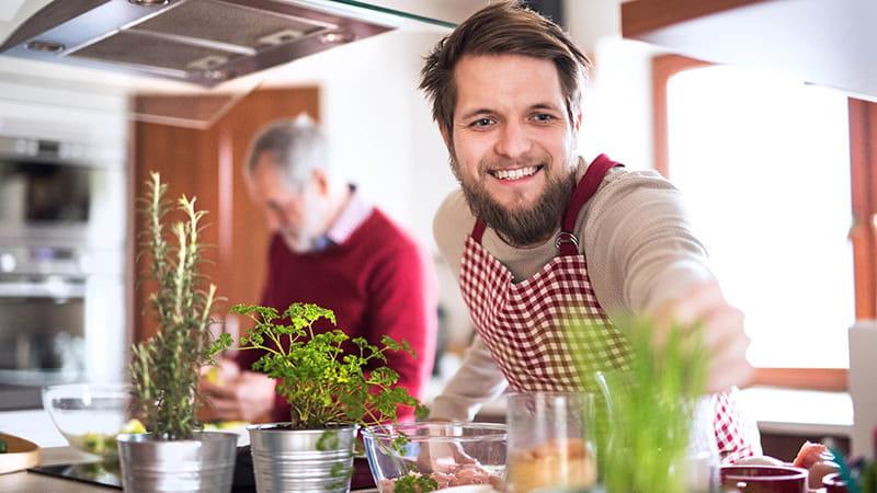 hijo hípster cocina junto a su padre