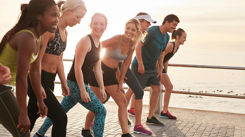 Grupo de personas sonriendo en la playa y preparándose para una carrera