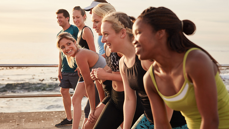 Group of multi-ethnic young adults starting a race on the beach