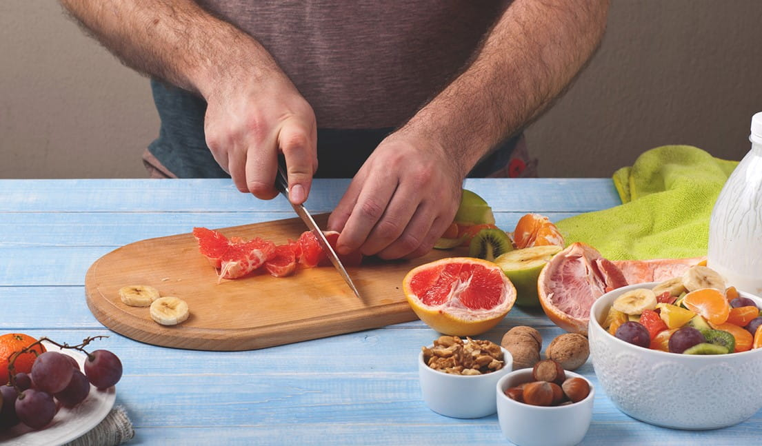 Person cutting fruit on a cutting board