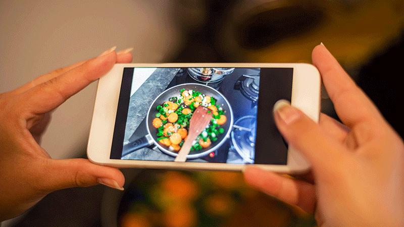 manos de mujer con teléfono inteligente toma fotografías de comida