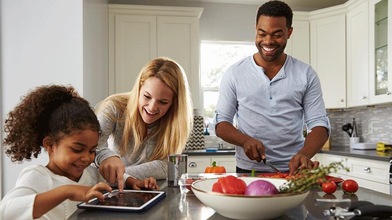Una familia diversa comiendo en la cocina y usando una tableta