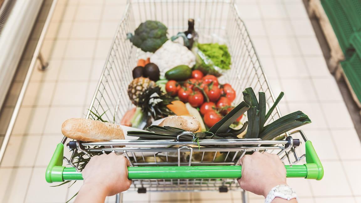 manos empujando el carrito de supermercado por un pasillo de la tienda