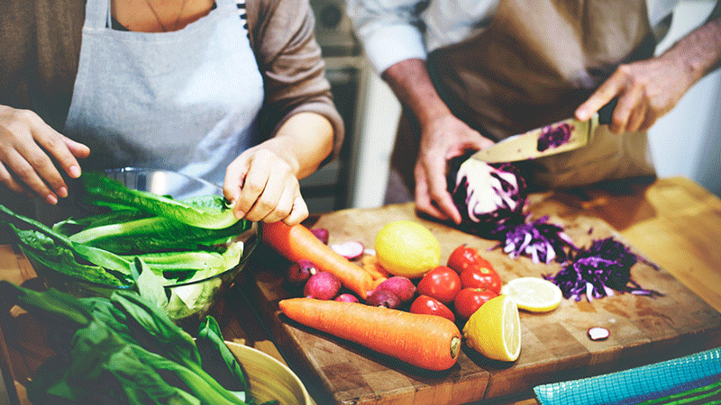 Pareja picando verduras en la tabla de cortar