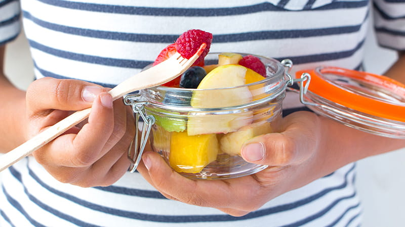 close up of hands eating fruit in a mason jar with fork