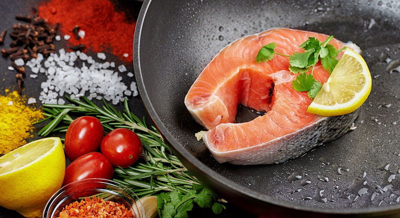 Salmon steak in a cast iron skillet surrounded by vegetables