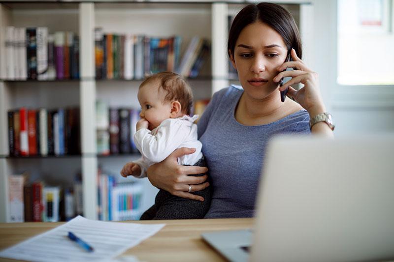 Una mamá ocupada trabajando con un teléfono celular y una computadora portátil que sostiene a su bebé