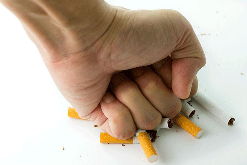 dejar de fumar; mano aplastando cigarrillos